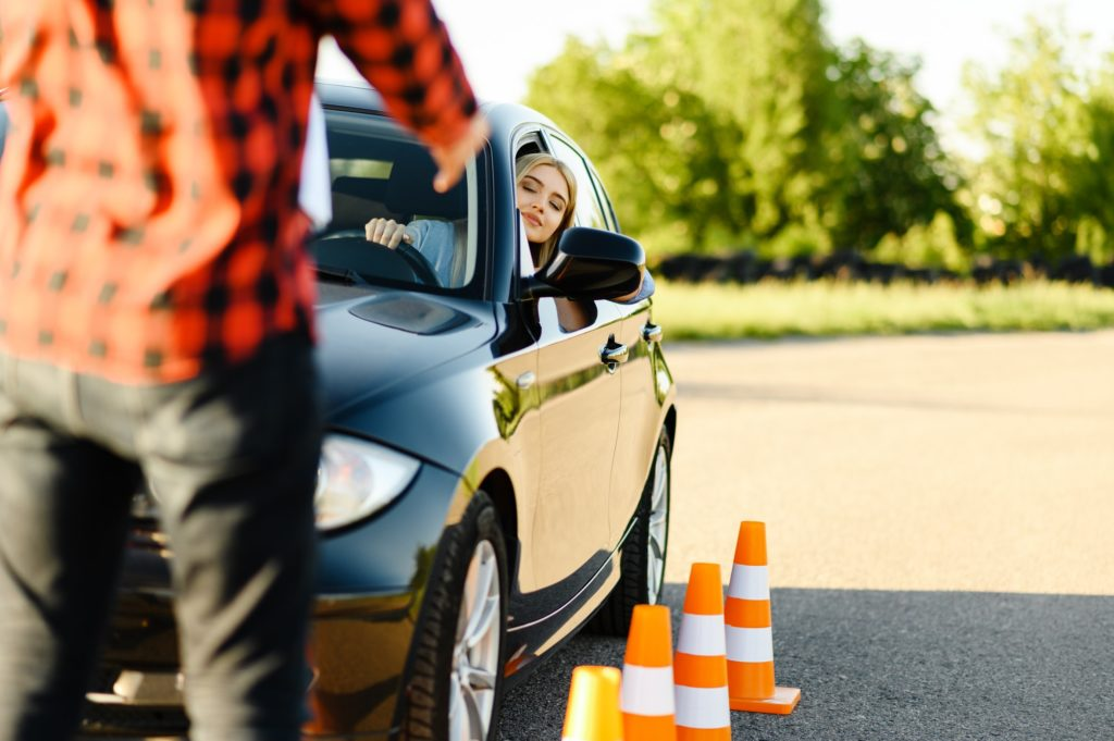 Male instructor and woman in car, traffic cones